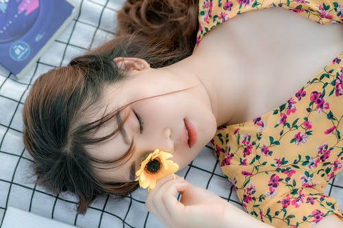 From above of young relaxed Asian female lying on blanket on sunny day and covering eye with fresh yellow flower
