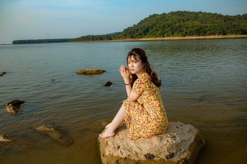 Calm young ethnic woman siting on stone in lake