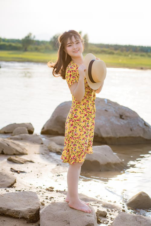 Side view of happy young barefooted Asian female tourist in dress standing on rocky shore of lake with straw hat in hand and smiling