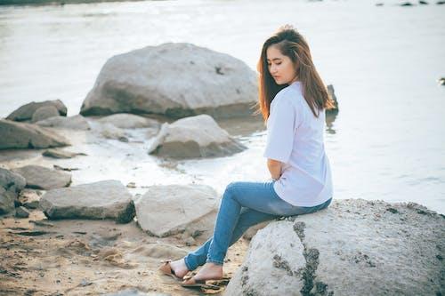 Calm Asian woman near river in summer