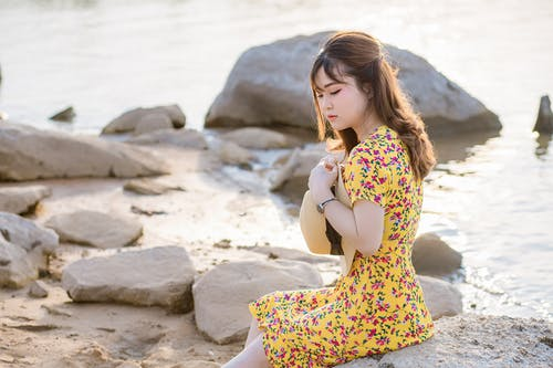 Serene young ethnic lady resting on sea beach during sunset