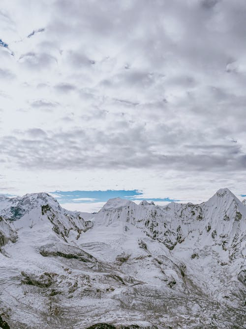 Snow Capped Mountains Under the Cloudy Sky