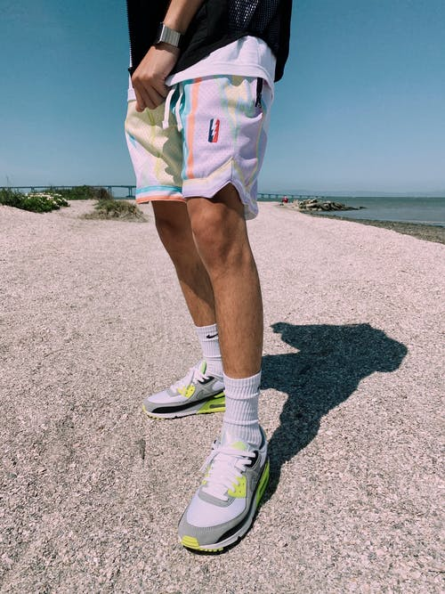 Crop unrecognizable young male athlete in stylish sportswear standing on sandy ground near sea during outdoor training on sunny day