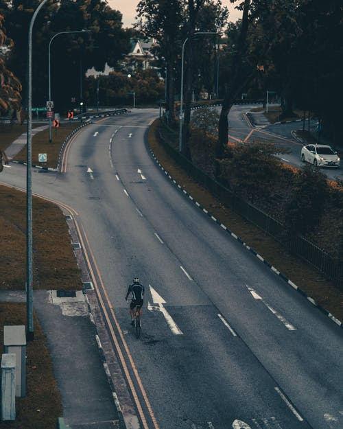 From above of distant unrecognizable person riding bicycle along empty asphalt road during sunrise