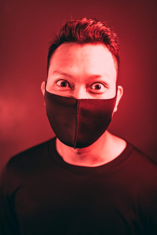Man with dark hair and bulging eyes wearing black medical mask and sweater in room with red light