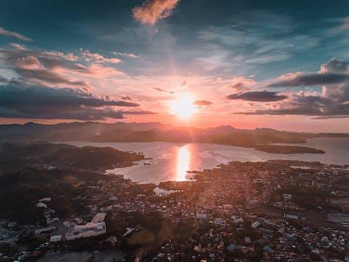Bright sun over sea and coastal city during sundown