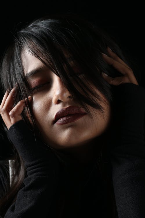 Pensive young female with makeup and dark hair touching head while sensually in dark