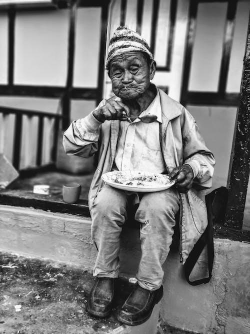 Black and white full body of ethnic senior homeless male having lunch sitting on street