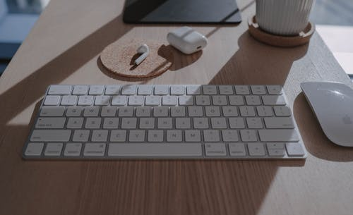 Apple Keyboard on Brown Wooden Table