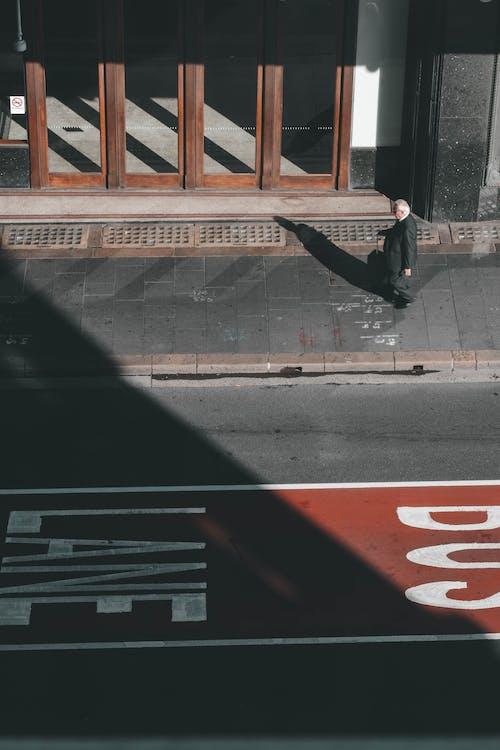Man in Black Jacket and Pants Standing on Sidewalk