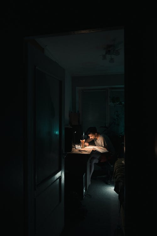 Student doing homework at table at night
