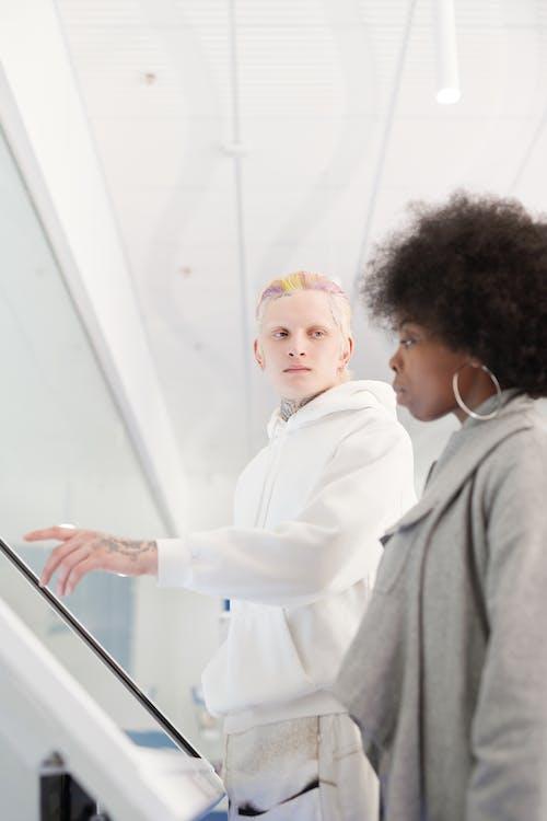 Man in White Dress Shirt Standing Beside Woman in Gray Coat