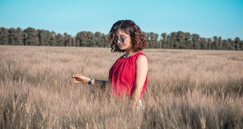 Young stylish woman in field at daytime