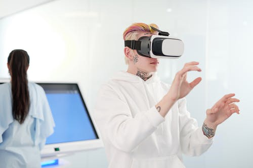 Woman in White Long Sleeve Shirt Holding Black and White Vr Goggles