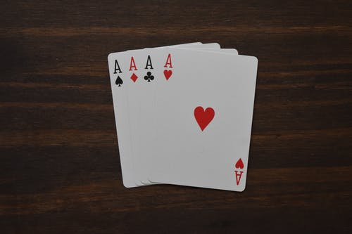 Top view of combination of four aces of different suits in poker on wooden table