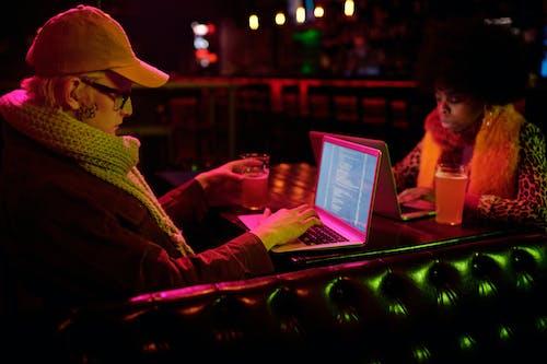 Man in Brown Hat and Brown Coat Using Macbook