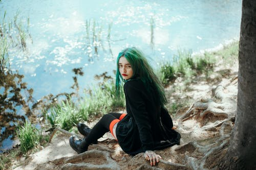 From above full body of pensive adolescent female in black coat and long stockings looking at camera over shoulder while chilling on roots of old tree on coast of lake in sunlight
