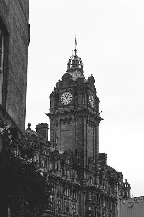Black and white of majestic clock tower of Balmoral Hotel in Edinburg in UK