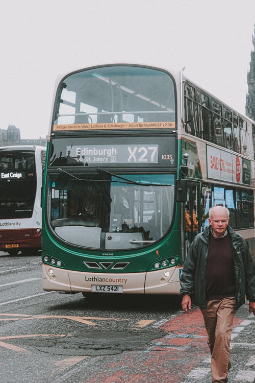 Tourist in front of double decker bus