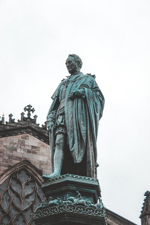 Statue of adult man in cloak