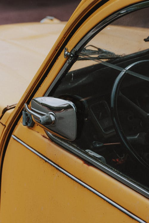 Metallic outside mirror and big round black wheel behind transparent window of retro car