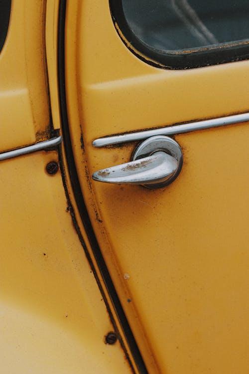 Small metallic rusty handle on side door of old yellow shabby retro car in daylight