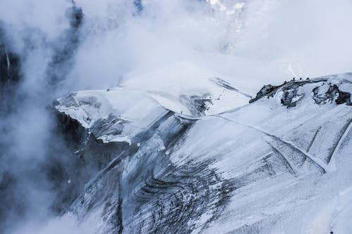 Majestic rough mountain range covered with snow under thick fog on high altitude