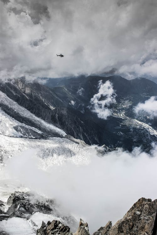 Amazing view of helicopter flying above rough mountains peaks covered with snow and fog against cloudy sky