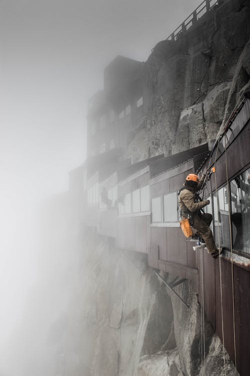 Side view faceless brave mountaineer in warm alpinist clothes hanging on ropes against modern wooden constructions slope mounted on rough rock during foggy weather