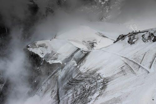 Stiff mountain slop under snow and fog