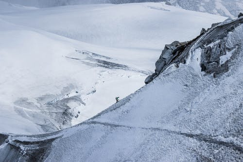 From above distant alpinist on snowy rough mountain slope against frozen spacious mountainous valley in daylight