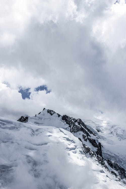 Rocky mountains with sharp peaks covered with snow and ice against majestic cloudy sky