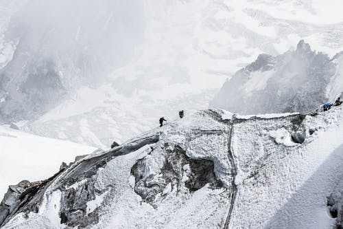 Distant alpinists trekking on snowy mountain slope