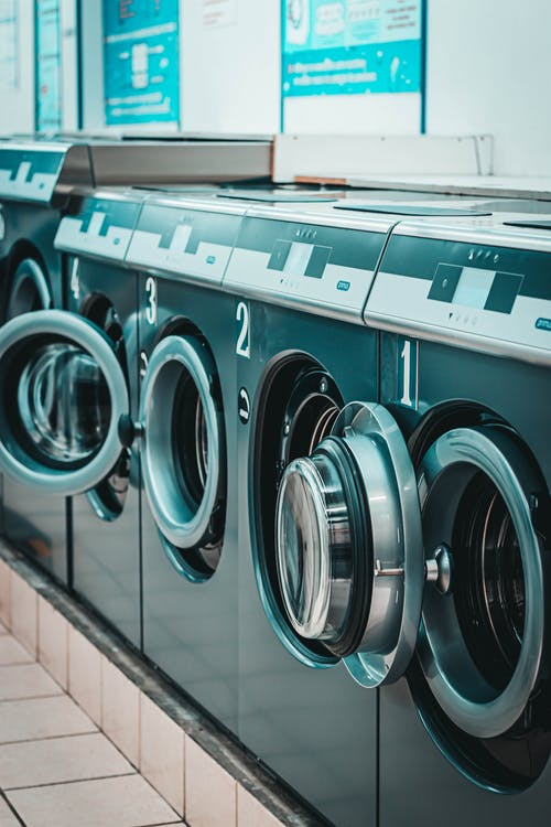 Row of modern washing machines in laundry