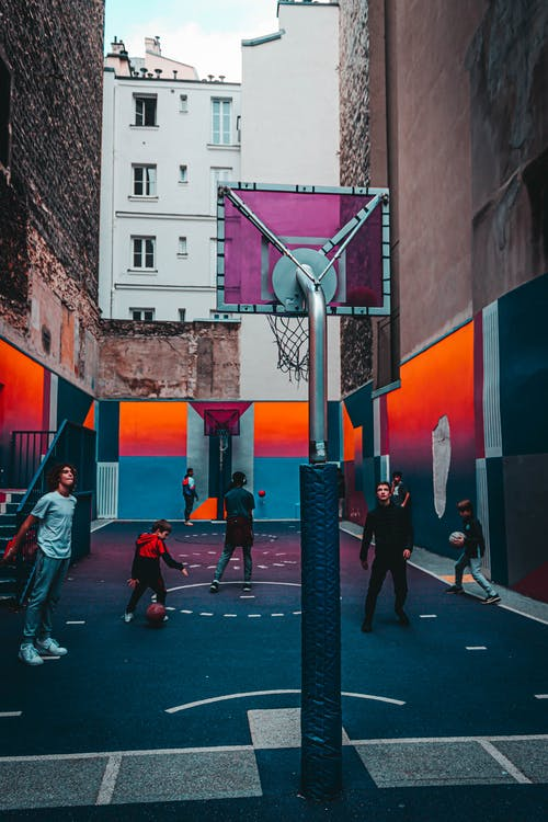 Teenagers playing basketball on street court