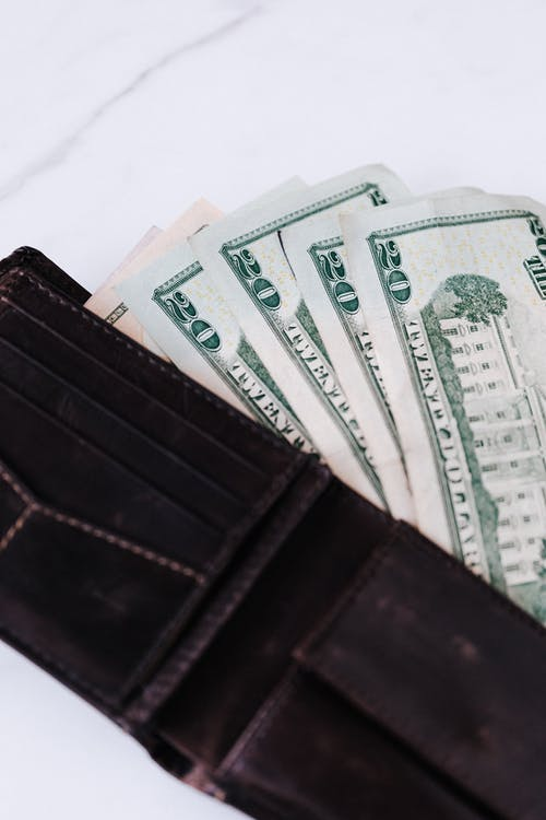 Black wallet with dollar banknotes
