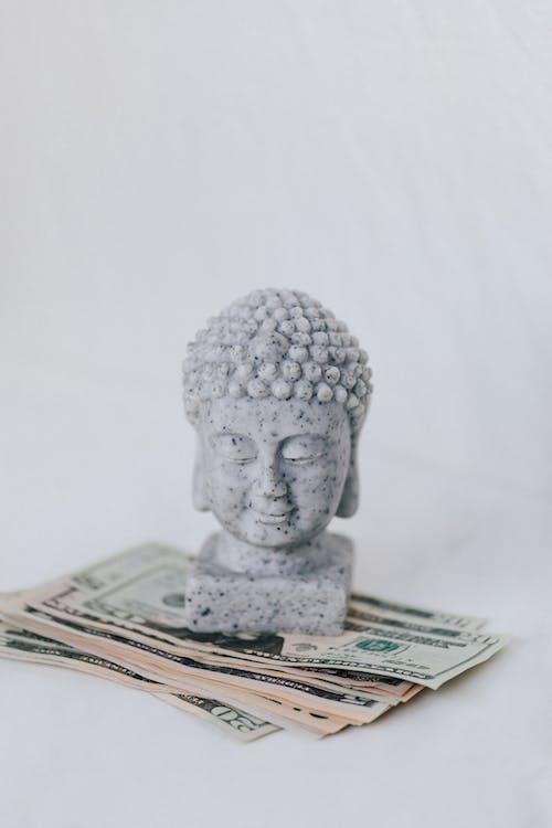Tibetan sculpture on heap of American dollars on white background