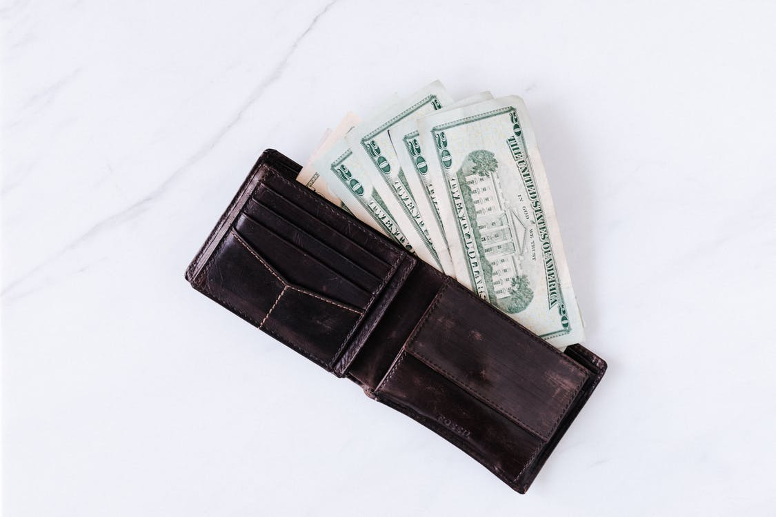 Wallet with pile of American paper dollars