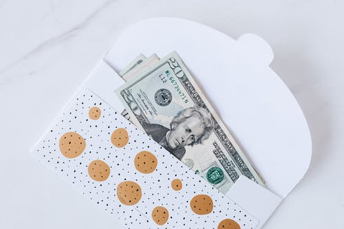 Money envelope with American dollar banknotes on white surface
