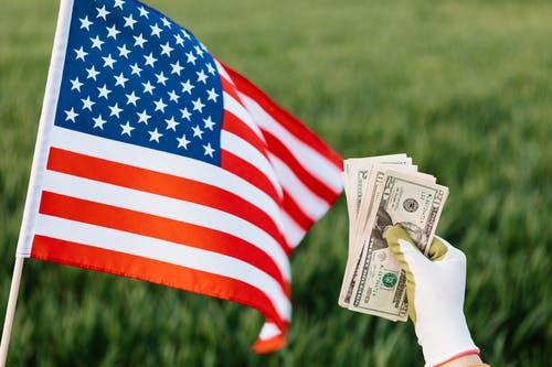 American flag and crop unrecognizable person with pile of dollars