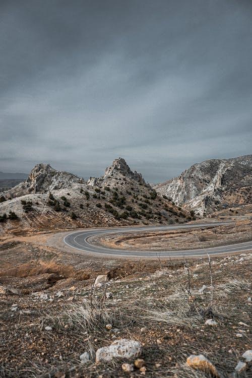 Asphalt road through mountainous stony valley