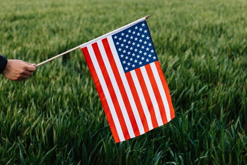 Crop faceless person holding spiky stick with American flag representing stripes and stars of bright colors on field with growing grass in daylight