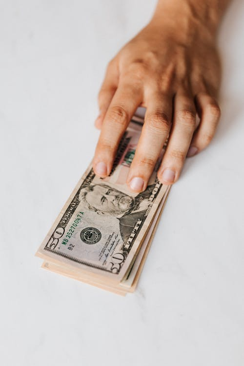 Crop faceless person putting pile of paper money on table