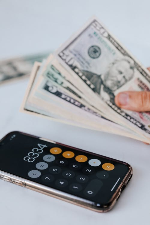From above of crop anonymous person holding heap of American dollar near cellphone with calculator application representing numbers