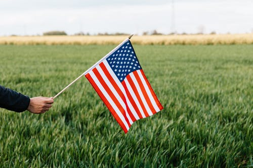 Crop unrecognizable person holding colorful flag of America with stars and stripes on lush green lawn under cloudy sky in daylight