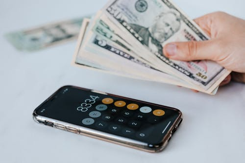 Calculator application on mobile phone screen on white surface near crop anonymous person holding pile of dollars