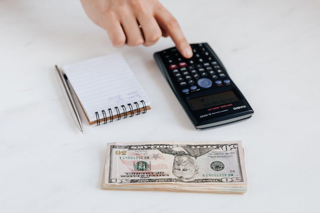 Crop unrecognizable accountant using calculator near pile of American dollars
