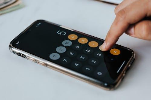 Crop anonymous economist using calculator app on smartphone at work