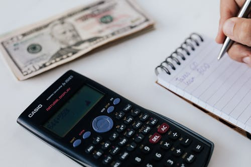 Crop unrecognizable accountant counting savings using notebook and calculator