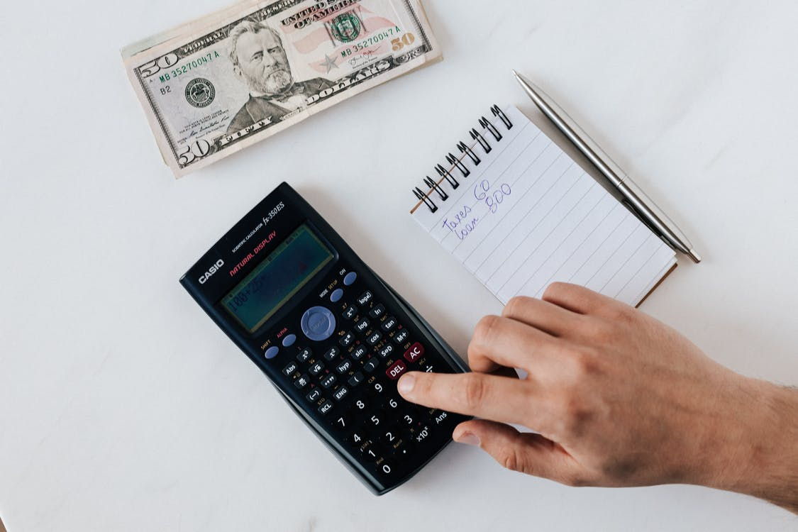 Crop faceless accountant using calculator while making budget